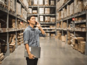 supply chain management a man on the phone with his manager in a warehouse