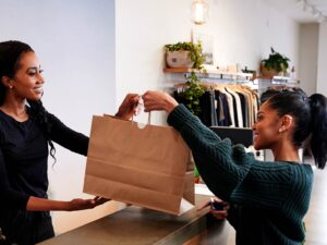 a woman handing over bought items in a bag in a retail store